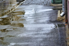 Frau im Garten Fallender Regen regentropfen Pfützen mit Blasen auf der Pflasterung Nasser Asphalt Schlechtes Wetter Regenjahresze Stockfotos