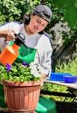 Frau im Garten mit Blumen Stockfotografie