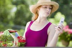 Frau im Garten mit Handy Stockfotos