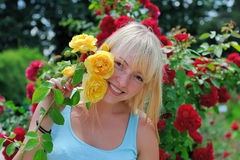 Frau im Garten mit Rosen lizenzfreie stockbilder