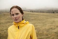 Frau im Gelb auf regnerischem Tageslauf lizenzfreie stockfotos