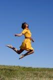 Frau im gelbem Kleidspringen Stockbilder