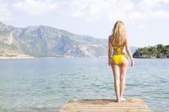 Frau im gelben Bikini-Stand am See-Rand Stockfotografie