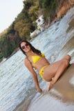 Frau im gelben Bikini am Strand stockbild