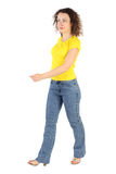 Frau im gelben Hemd und in den Jeans nach links gehend Stockbilder