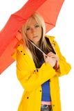 Frau im gelben Regenmantel unter dem roten Regenschirm ernst lizenzfreie stockbilder