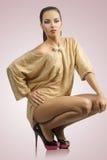 Frau im Goldkleid und -hohen Absätzen Stockfotografie