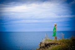 Frau im grünen Kleid und im Meer Stockfotografie