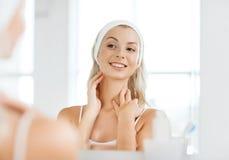 Frau im Hairband, der ihr Gesicht am Badezimmer berührt stockfotos
