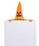 Frau im Halloween-Hut, der heraus von der Anschlagtafel schaut Lizenzfreies Stockfoto
