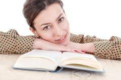 Frau im Hemd, das auf Buch und träumerischem in Ca gerade schauen sich lehnt Stockfoto