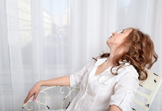 Frau im Hemd, das auf einem Stuhl vor dem Fenster sitzt Stockbild