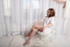 Frau im Hemd, das auf einem Stuhl vor dem Fenster sitzt Lizenzfreies Stockfoto