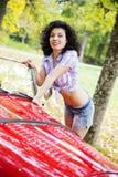Frau im Hemd, das auf Retro- Autoseite aufwirft stockfotografie