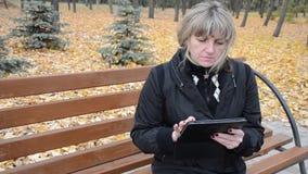 Frau im Herbstpark, der mit der Tablette arbeitet stock video footage