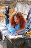 Frau im Herbstpark Lügen auf einer Bank mit einem Schleier und Ablesen eines Buches Rot und Orange färbt Efeublattnahaufnahme stockfotos