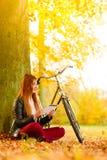 Frau im Herbstpark unter Verwendung der Tablet-Computer-Lesung Stockfotografie