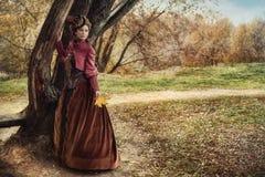 Frau im historischen Kleid nahe dem Baum im Herbstwald Stockfotografie