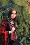 Frau im Holz mit Regenschirm Stockfotografie