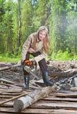 Frau im Holz sägt einen Baum eine Kettensäge Lizenzfreies Stockfoto
