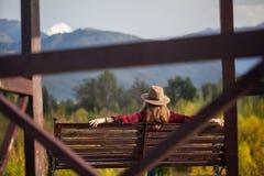 Frau im Hut auf der Bank Lizenzfreies Stockbild