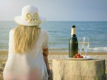 Frau im Hut in dem Meer mit einer offenen Flasche Champagner und zwei Gläsern Stockfotografie