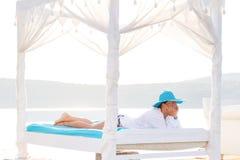 Frau im Hut, der auf Bett in dem Meer sich entspannt Stockbilder