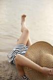 Frau im Hut, der auf dem Strand liegt Stockfotografie