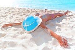 Frau im Hut, der auf dem Strand sich entspannt Lizenzfreie Stockfotografie
