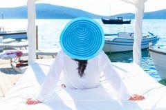 Frau im Hut, der auf weißem Luxusbett sich entspannt Stockbilder
