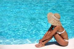 Frau im Hut, der neben Pool sich entspannt Stockfoto
