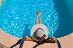 Frau im Hut, der am Pool sich entspannt Lizenzfreie Stockbilder