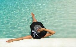 Frau im Hut, der am Pool sich entspannt Stockfoto