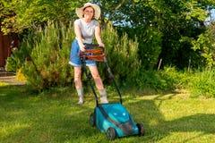 Frau im Hut mit elektrischem Rasenmäher auf Gartenhintergrund lizenzfreie stockfotografie