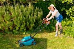 Frau im Hut mit elektrischem Rasenmäher auf Gartenhintergrund Lizenzfreie Stockfotos