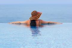 Frau im Hut am Pool Stockfotos