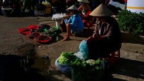 Frau im Hut sitzt Verkaufs-Grüns am Straßenmarkt- in Vietnam stock video