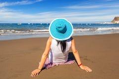 Frau im Hut Sonnenfeiertage auf dem Strand genießend Stockfotografie