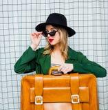 Frau im Hut und im grünen Mantel in der Art 90s mit Reisekoffer stockfotografie