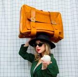 Frau im Hut und im grünen Mantel in der Art 90s mit Reisekoffer und -Sparschwein stockbilder