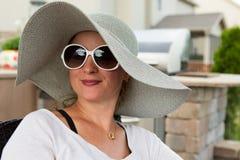 Frau im Hut und in Sonnenbrille, die auf hinterem Patio sitzen stockfoto