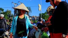 Frau im Hut verkauft Gemüse auf Straßenmarkt- in Vietnam stock footage