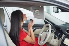 Frau im Innen Auto hält Rad, um lächelnde schauende Passagiere im Rücksitzideen-Taxifahrer gegen sich zu wenden stockbild