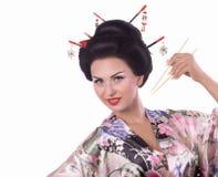 Frau im japanischen Kimono mit Essstäbchen und Sushirolle Lizenzfreies Stockbild