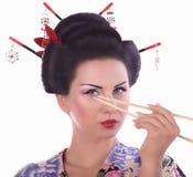 Frau im japanischen Kimono mit Essstäbchen und Sushirolle Lizenzfreie Stockbilder