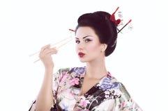 Frau im japanischen Kimono mit Essstäbchen und Sushirolle Stockfotografie