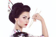 Frau im japanischen Kimono mit Essstäbchen und Sushirolle Lizenzfreie Stockfotografie
