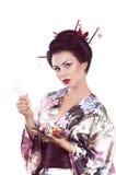 Frau im japanischen Kimono mit Essstäbchen und Sushirolle Stockfoto