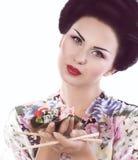 Frau im japanischen Kimono mit Essstäbchen und Sushirolle Lizenzfreie Stockfotos