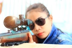Frau im Jeansanzug und in tragender Sonnenbrille mit dem Schießstand schoss von einem Gewehrgewehr stockfoto